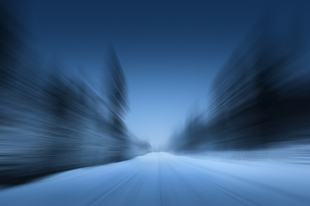 blured road in winter forest photo