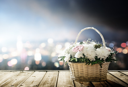 flowers in basket and lights of night city photo