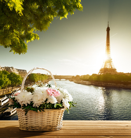 romantic sky: flowers in basket and Eiffel tower, Paris Stock Photo