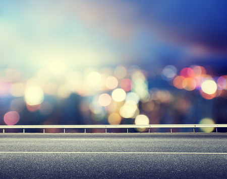 night road: Asphalt road and blurred modern city Stock Photo