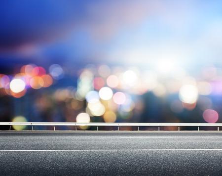 Asphalt road and blurred modern city photo