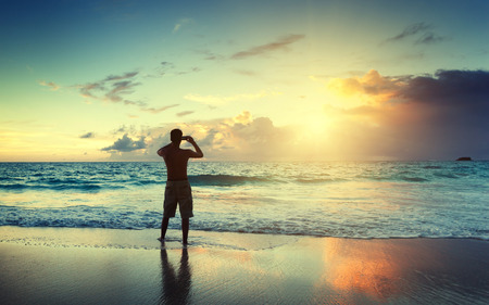 young man on the beach take photo on mobile phone photo