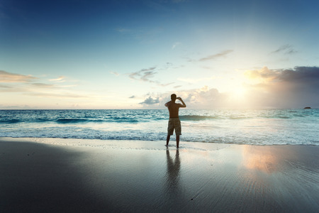 young man on the beach take photo on mobile phone Stock Photo