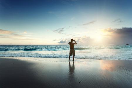 hombre joven en la playa tome la foto en el teléfono móvil