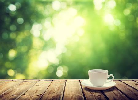 コーヒー カップと日当たりの良い木の背景 写真素材