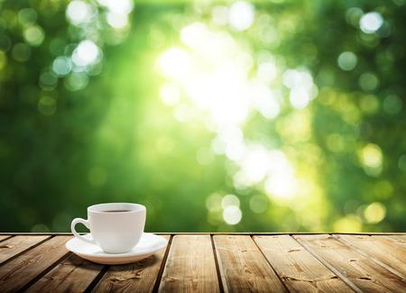 wooden desk: kopje koffie en zonnige bomen achtergrond Stockfoto