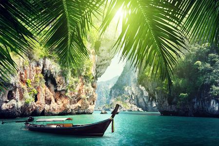 長いボートの上や岩のビーチ クラビ、タイで 写真素材