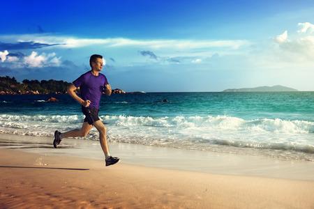 persona saltando: Hombre que se ejecuta en la playa tropical al atardecer