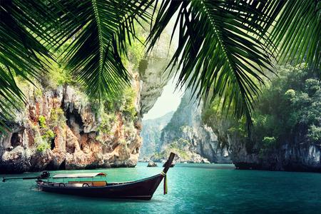 lange boot en rotsen op het strand in Krabi, Thailand