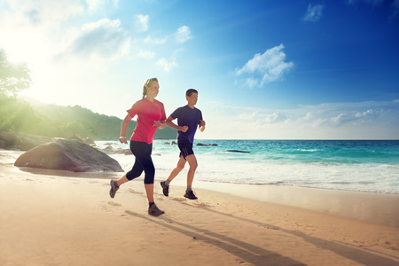 Man and woman running on tropical beach at sunset  photo