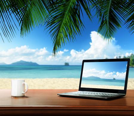 notebook: notebook op tafel en tropisch strand Stockfoto