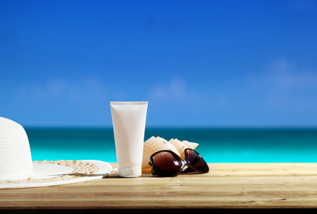 Sun lotion and sunglasses on the beach photo