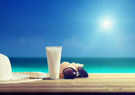 sun protection: Sun lotion and sunglasses on the beach