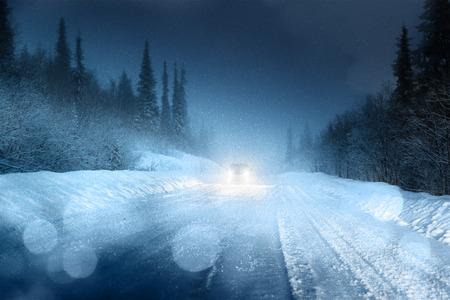january sunrise: Las luces del coche en el bosque de invierno Foto de archivo