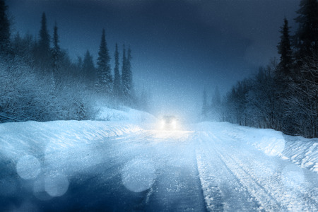 Car lights in winter forest