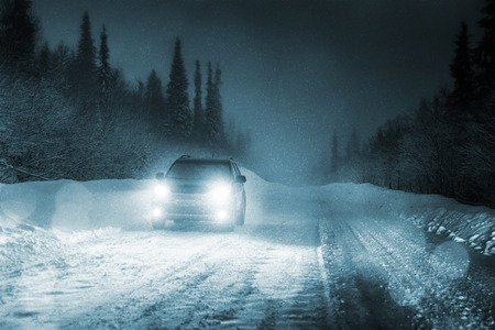 Car lights in winter forest photo