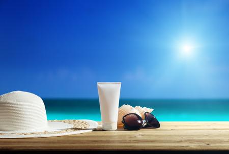 Sun lotion and sunglasses on the beach