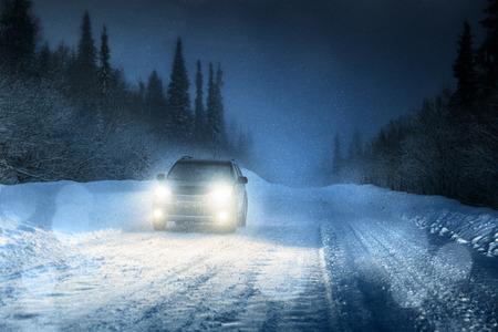 Autolichten in de winterbos Stockfoto