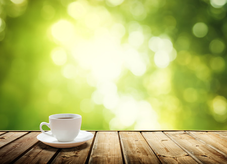 table food: cup coffee and sunny trees background