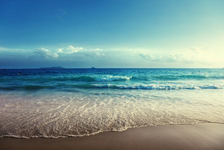 vague: seychelles plage dans le temps du coucher du soleil