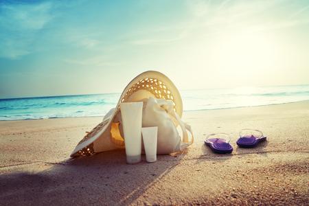 spray: crema solar, sombrero con bolsa en la playa tropical Foto de archivo