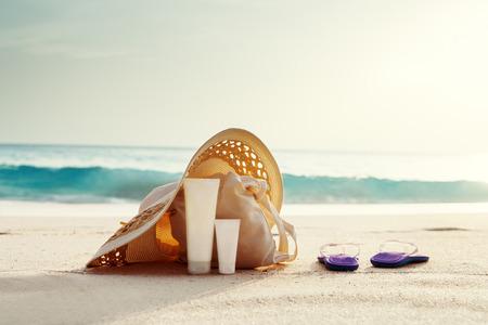 Crème solaire, chapeau avec sac à la plage tropicale