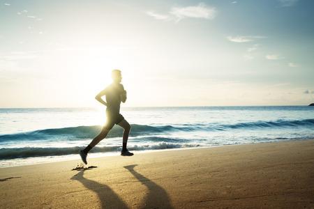 夕暮れ時に熱帯のビーチで走っている人