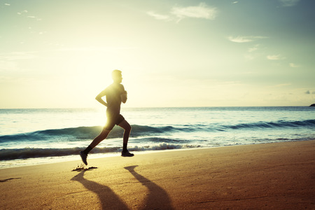 Man running on tropical beach at sunset Stock Photo