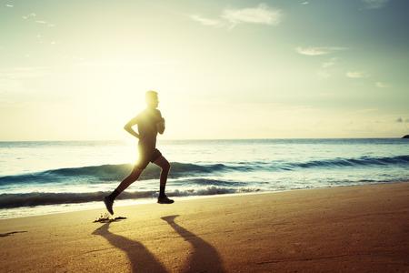 Mens die op tropisch strand bij zonsondergang loopt