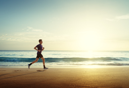 Man running on tropical beach at sunset Banque d'images