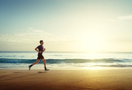 Man draait op tropisch strand bij zonsondergang Stockfoto - 56410885