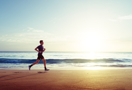 Man running on tropical beach at sunset Stockfoto