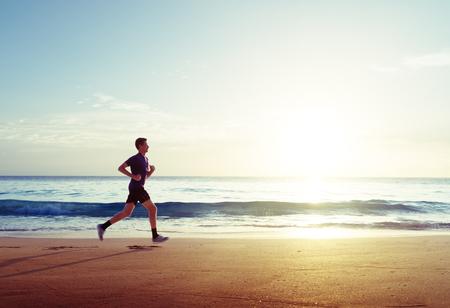 Man running on tropical beach at sunset Standard-Bild