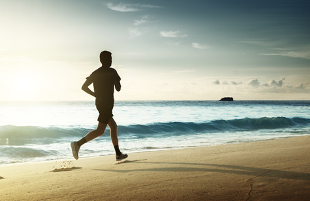 blue sea: Man running on tropical beach at sunset Stock Photo