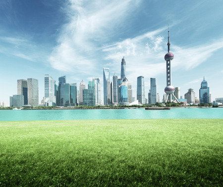 river: Shanghai skyline and green grass in park, China