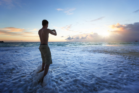 man taking photos of sunset on tropical beach by smartphone photo