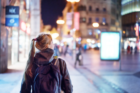 Back view of girl walking on city street at night, Prague Foto de archivo