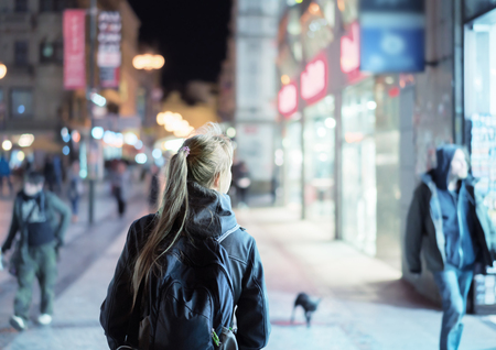 retail scene: Back view of girl walking on city street at night, Prague Stock Photo