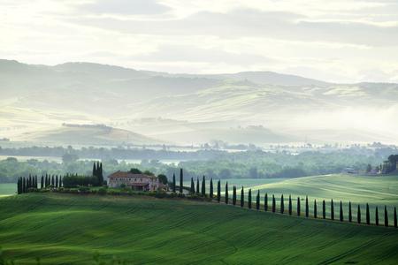 Tuscany countryside panorama, green field and farm house, Italy Stock Photo