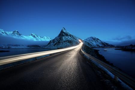 Olstind Mount and car light. Lofoten islands, spring time, Norway