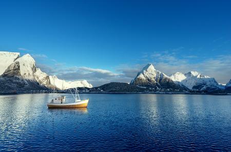 Fishing boat and Reine Village, Lofoten Islands, Norway Stock Photo