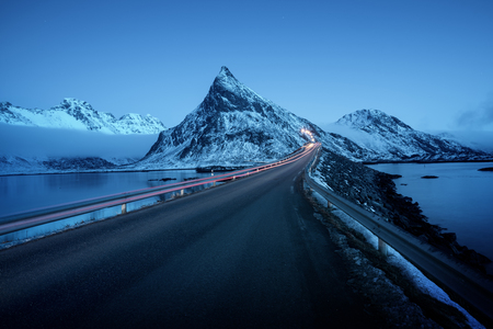 Olstind Mount and car light. Lofoten islands, spring time, Norway
