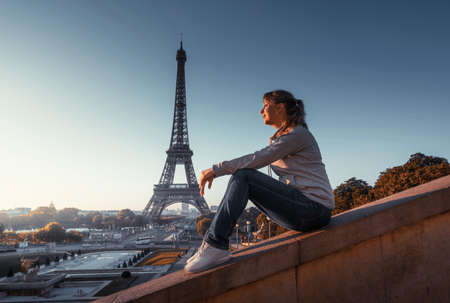 woman and Eiffel tower in sunrise time, Paris, France 写真素材