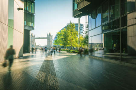 business people, modern buildings and Tower Bridge, London, UK