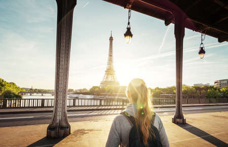woman tourist walking in front of the Eiffel Tower in Paris, France