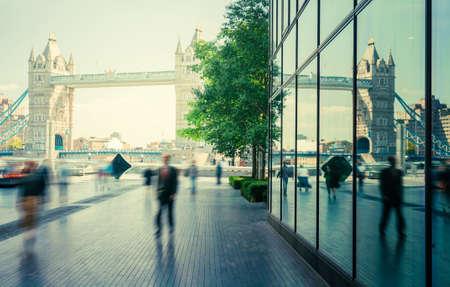 business people, modern buildings and Tower Bridge, London, UK