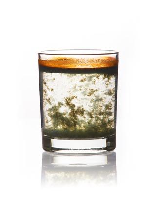 acqua vetro: acqua tossica. vetro riempito di acqua sporca con un precipitato giallo-verde