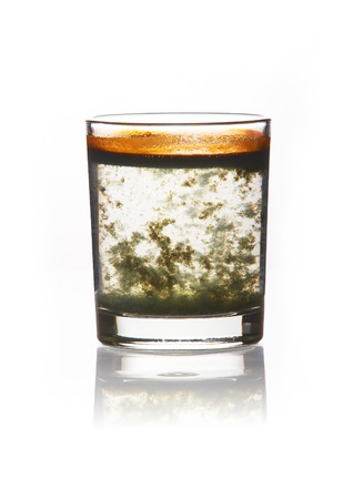 toxic substance: toxic water. glass filled with dirty water with a yellow-green precipitate