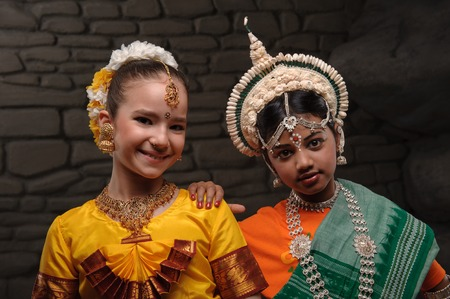 yashmak: international friendship. girls dancing, dressed in traditional Indian attire. Europeans and Indian friendship against stones Stock Photo