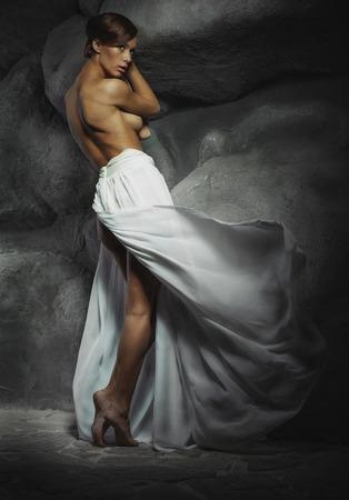 chica sexy en blanco falda larga con la espalda y las piernas desnudas, con las piedras en el fondo. Foto de la moda